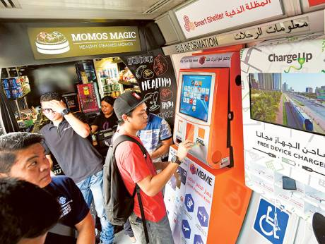 Image Credit: Virendra Saklani/Gulf News Mobile phone charging ports, the smart payment service kiosk and the food and beverage counter at new RTA smart bus shelter in Satwa.